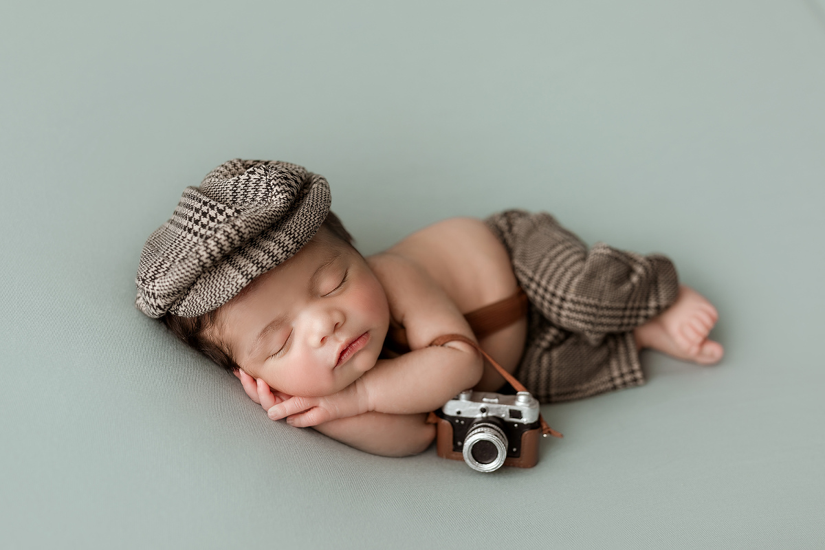 newborn baby holding a camera prop while being photographed